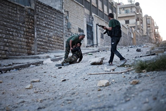 FSA soldiers help a severely wounded colleague after being shot by a Syrian Army sniper in Izaa district in Aleppo, Syria, Saturday, Sept 8, 2012. On Friday, U.S. Senators John McCain, Joe Lieberman and Lindsay Graham, who have toured the volatile Middle East in recent days, urged Washington to help arm Syria&#39;s rebels with weapons and create a safe zone inside the country for a transition government. (AP Photo/ Manu Brabo)