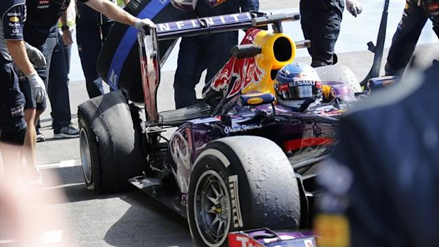 Mechanics look at the damaged tyre of Red Bull Formula One driver Sebastian Vettel (Reuters0