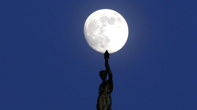 "The moon in its waxing gibbous stage shines over a statue entitled ""Enlightenment Giving Power"" by John Gelert, which sits at the top of the dome of the Bergen County Courthouse in Hackensack, N.J., Friday, June 21, 2013. The moon, which will reach its full stage on Sunday, is expected to be 13.5 percent closer to earth during a phenomenon known as supermoon. (AP Photo/Julio Cortez)"