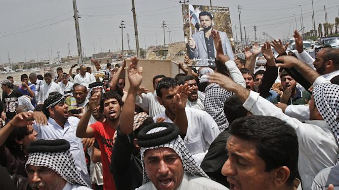 Family members of Diaa Mutashar al-Issawi, seen in the poster, chant anti-Jabhat al-Nusra and Free Syrian Army slogans during his funeral in Basra, Iraq's second-largest city, 340 miles (550 kilometers) southeast of Baghdad, Iraq, Monday, May 6, 2013. The Iraqi Shiite fighter's body was collected Monday morning at a border crossing with Iran, then carried through the streets of this southern Iraqi city as mourners vowed a similar sacrifice to protect a revered shrine in Syria. (AP Photo/ Nabil Al-Jurani)