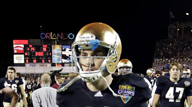 Notre Dame quarterback Tommy Rees walks off the field after losing to Florida State 18-14 in the Champs Sports Bowl NCAA college football game, Thursday, Dec. 29, 2011, in Orlando, Fla.(AP Photo/John Raoux)