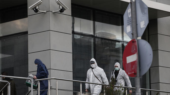 Greek Police forensic experts walk outside the New Democracy party headquarters after an unknown attacker fired an automatic rifle at the building on the capital's busy Syngrou Avenue, Athens, on Monday, Jan. 14, 2013. A gunman fired a spray of bullets at the headquarters of the governing center-right New Democracy party near central Athens early Monday, with one hitting an office occasionally used by the prime minister, officials said. No one was hurt. (AP Photo/Petros Giannakouris)