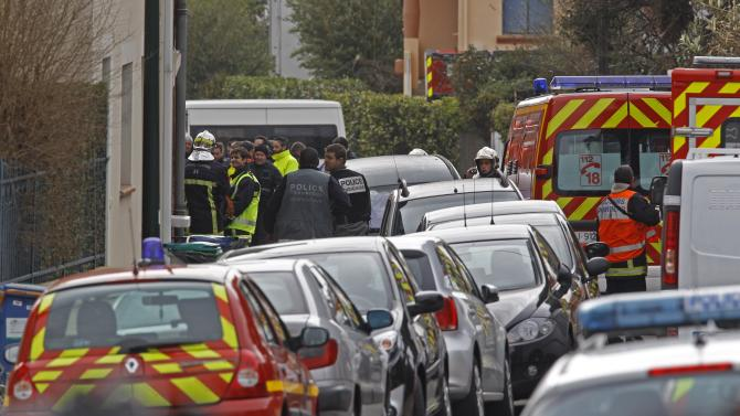 Police officers and firefighters stand next to the building where the suspected killer is holed-up  in Toulouse Wednesday March 21, 2012 .  After a pre-dawn raid erupted into a firefight, French riot police pressed Wednesday for the surrender of a holed-up gunman who is suspected in seven killings and claiming allegiance to al-Qaida. A prosecutor said the gunman was planning to kill another soldier imminently.(AP Photo/Remy de la Mauviniere)