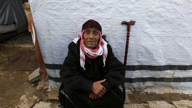 An elderly Syrian refugee woman sits near her tent at a refugee camp in Zahle in the Bekaa valley
