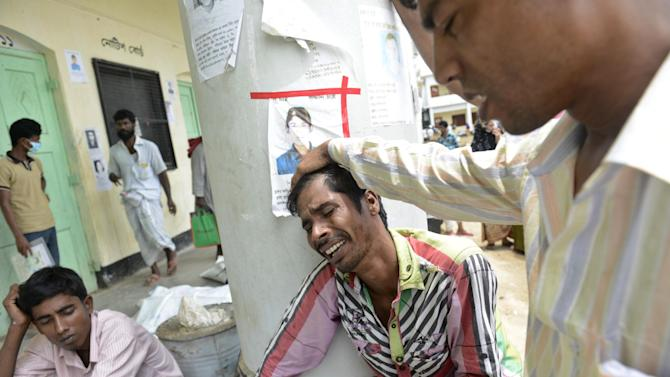 A Bangladeshi man mourns after identifying the body of a relative at a makeshift morgue in Savar, near Dhaka, Bangladesh, Saturday May 11 2013. The death toll from Bangladesh's worst industrial disaster is more than 1,000 and climbing. More than 2,500 people were rescued in the immediate aftermath of the April 24 disaster. (AP Photo/Ismail Ferdous)