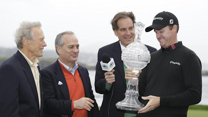 Jimmy Walker, right, looks over his trophy after it was presented to him by actor and director Clint Eastwood, left, on the 18th green of the Pebble Beach Golf Links after winning the AT&T Pebble Beach Pro-Am golf tournament Sunday, Feb. 9, 2014, in Pebble Beach, Calif. AT&T CEO Andy Geisse, second from left, and broadcaster Jim Nantz, second from right, look on