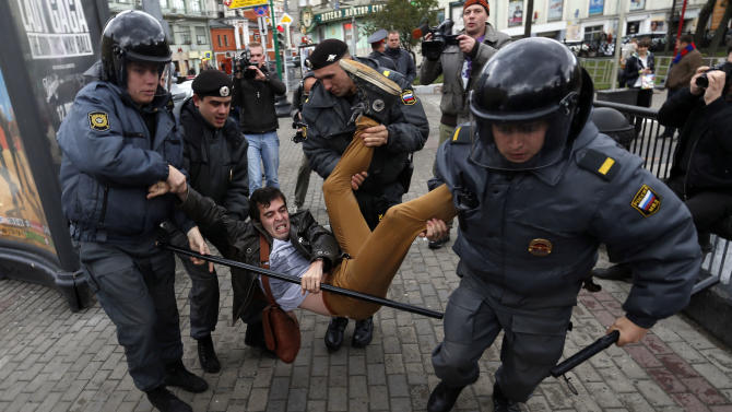 Police officers detain political activist Roman Dobrokhotov during the unauthorized meeting to mark Russian President Vladimir Putin's birthday in Moscow, Sunday Oct. 7, 2012. Vladimir Putin turns 60-years old on Sunday, Oct. 7, 2012, and has recently sought to demonstrate his youthful vigor by many personal endeavors, but while he has shown creativity in his action-man stunts, the Russian president seems surprisingly vulnerable to the vagaries of oil prices. (AP Photo/Sergey Ponomarev)