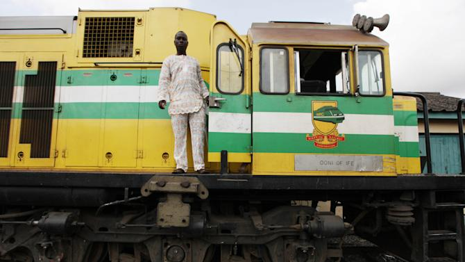 In this Photo taken, Friday, March . 8, 2013, A train driver stand on an Ooni of Ife train to Kano, in Lagos, Nigeria.  Nigeria reopened its train line to the north Dec. 21, marking the end of a $166 million project to rebuild portions of the abandoned line washed out years earlier. The state-owned China Civil Engineering Construction Corp. rebuilt the southern portion of the line, while a Nigerian company handled the rest. The rebirth of the lines constitutes a major economic relief to the poor who want to travel in a country where most earn less than $1 a day. Airline tickets remain out of the reach of many and journeys over the nation's crumbling road network can be dangerous. The cheapest train ticket available costs only $13. ( AP Photo/Sunday Alamba)