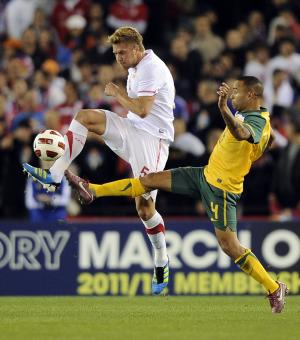 Serbia's Slobodan Rajkovic, left, and Archie Thompson of Australia compete for the ball during their friendly soccer match in Melbourne, Australia, Tuesday, June 7, 2011. (AP Photo/Andrew Brownbill)