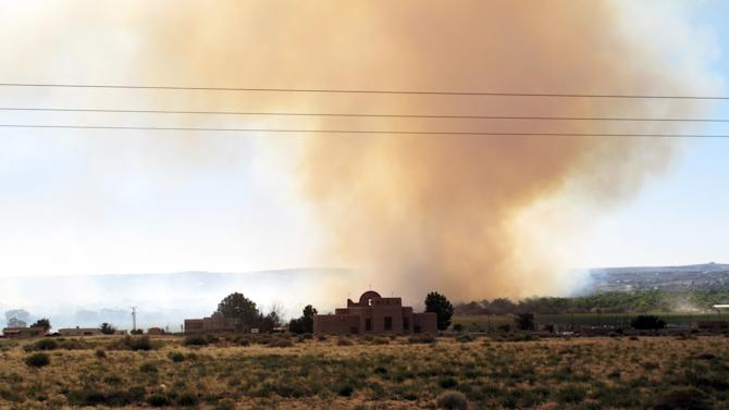 A wildfire rages in Corrales, N.M. along both sides of the Rio Grande just north of Albuquerque, N.M. Wednesday June 20, 2012. Officials say the fire in the wooded area had charred around 50 acres and some residents in Corrales and the Sandia Pueblo were told to prepare to evacuate. (AP Photo/Russell Contreras)