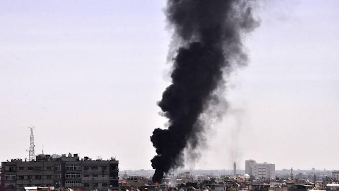 In this photo released by the Syrian official news agency SANA, black smoke rises from the rooftop of a building that was, according to SANA, attacked by a mortar shelled by the Syrian rebels in Damascus, Syria, Saturday, April 5, 2014. Al-Qaida's leader, Ayman al-Zawahri, called on fighters to determine who killed his chief representative in Syria, a man many militant groups believe died at the hands of a rival militia, in a move that highlighted a conflict between rebels that has killed hundreds. (AP Photo/SANA)
