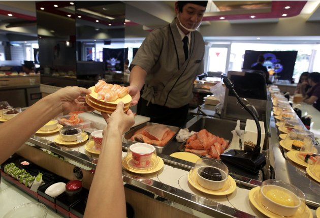 Chef hands a plate of sushi to a customer at a sushi bar in the Ximending shopping district of Taipei