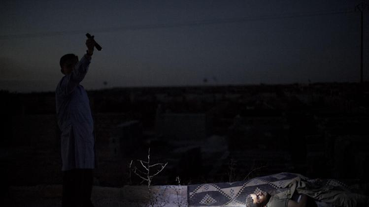 FILE - A man points a flashlight toward the body of a Syrian man killed from Syrian Army shelling at a graveyard in Aleppo, Syria, Saturday, Oct. 13, 2012. (AP Photo/Manu Brabo, File)