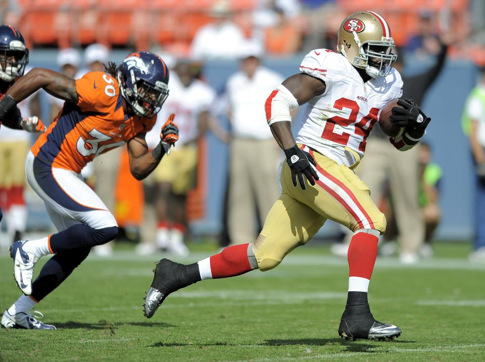 San Francisco 49ers running back Anthony Dixon (24) gets away from Denver Broncos defensive back David Bruton (30) to score on a 26-yard touchdown run during the third quarter of an NFL preseason football game in Denver, Sunday, Aug. 26, 2012. (AP Photo/Jack Dempsey)