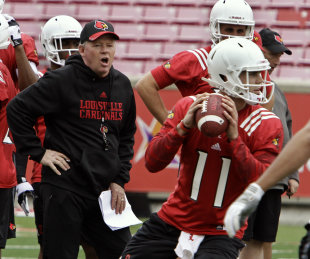 Bobby Petrino shouts instructions to his team as top returning QB Will Gardner (11) prepares to throw during spring practice. (AP)