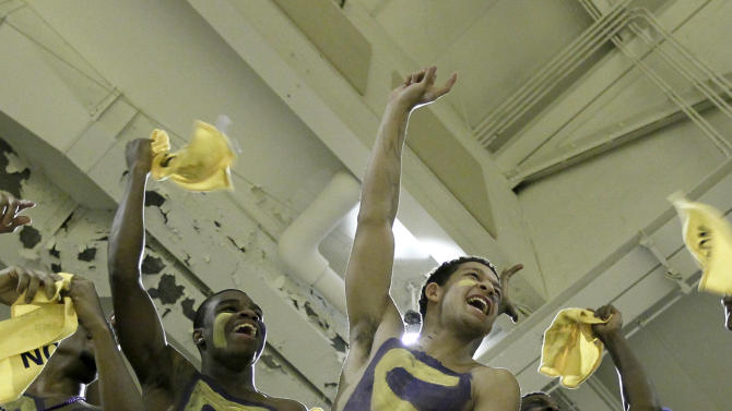 In this photo taken in Summit, Ill., on Friday, March 9, 2012, Students from Simeon Career Academy cheer on their team and carry a sign calling for Jabari Parker to Dunk It, during an Illinois sectional championship basketball game against Marist. (AP Photo/Charles Rex Arbogast)
