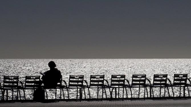 A woman sits on a bench on the Promenade Des Anglais in Nice
