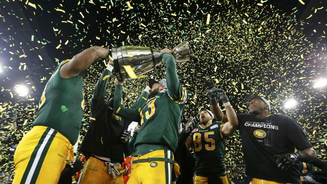 Edmonton Eskimos quarterback Mike Reilly raises the Grey Cup after his team defeated the Ottawa Redblacks in the CFL's 103rd Grey Cup championship football game in Winnipeg