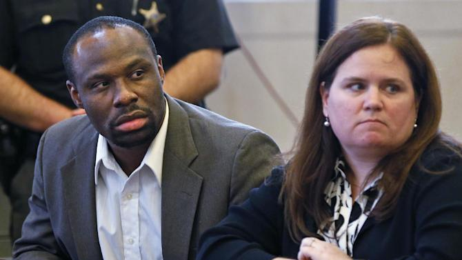 This photo made Thursday, May 16, 2013, in Cincinnati shows Ricardo Woods, left, sitting with attorney Wendy Calaway after he was found guilty in the shooting death of a man who authorities say identified his assailant by blinking his eyes while paralyzed. (AP Photo/The Cincinnati Enquirer, Gary Landers)