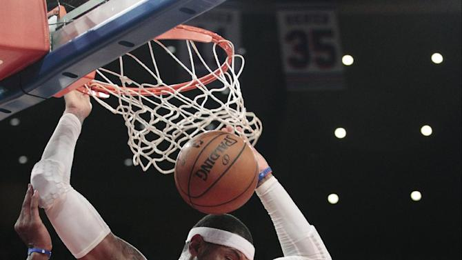 New York Knicks' Carmelo Anthony (7) dunks in front of Dallas Mavericks' Elton Brand during the first half of an NBA basketball game Friday, Nov. 9, 2012, in New York.  (AP Photo/Frank Franklin II)