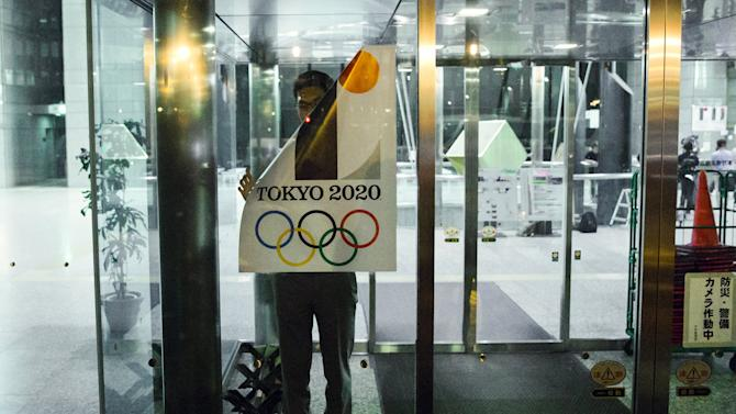 An employee takes down a placard with the Tokyo 2020 Olympic Games emblem during staged event for the media at the Tokyo Metropolitan Government Building in Tokyo