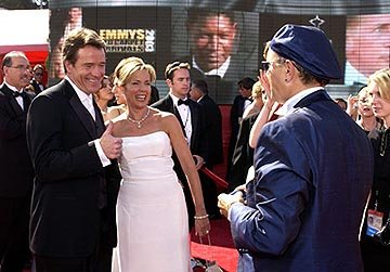 Bryan Cranston and his wife with Joe Pantoliano as Dennis Haysbertlooms large behind them