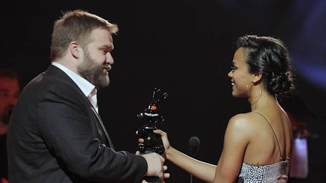 """Zoe Saldana, right, presents the award for game of the year to Robert Kirkman for """"Walking Dead: The Game"""" on stage at Spike's 10th Annual Video Game Awards at Sony Studios on Friday, Dec. 7, 2012, in Culver City, Calif. (Photo by Chris Pizzello/Invision/AP)"""