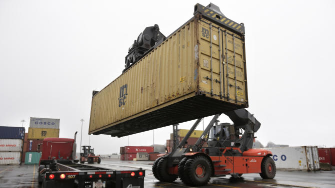In this photo taken Tuesday, Dec. 18, 2012, a reach stacker operated by a longshoreman, right, places a shipping container on a tractor trailer truck at the Port of Boston, in Boston. The longshoremen's union may strike if they are unable to reach an agreement on their contract that expires Dec. 29, 2012. (AP Photo/Steven Senne)