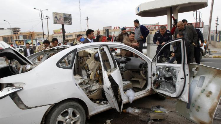 Iraqi security forces personnel inspect a car after a bomb in Kirkuk