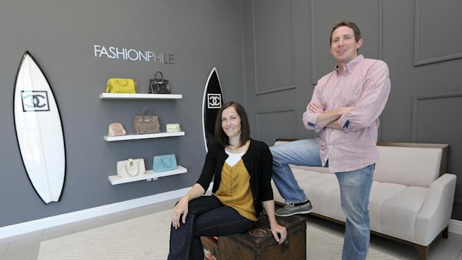This photo taken May 2, 2013, shows Sarah Davis and Ben Hemmnger, co-owners of Fashionphile.com posing in the lobby of their Carlsbad, Calif. office.  The internet company sells rare, vintage, and discontinued previous owned bags and is facing the complicated task of dealing with new state regulations on Internet sale taxes. (AP photo/Lenny Ignelzi)