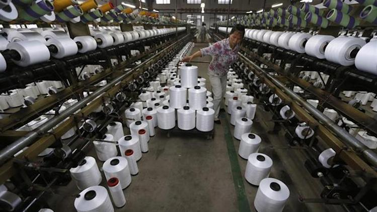 An employee works inside a textile factory in Linhai, Zhejiang province, May 30, 2013.