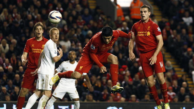 Liverpool's Luis Suarez, centre, scores against Swansea, during their English League Cup soccer match at Anfield Stadium, Liverpool, England, Wednesday Oct. 31, 2012. (AP Photo/Jon Super)