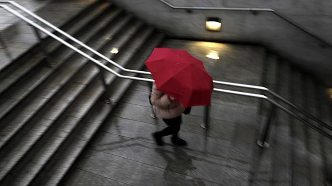 A woman holds an umbrella as she enters Syntagma Metro station during a rainfall  in Athens, on Friday, Jan. 25, 2013. Striking subway workers in Athens returned to the job Friday, hours after the Greek government used riot police to evacuate holdouts from a train depot, ending a bitter standoff over new austerity measures. (AP Photo/Petros Giannakouris)