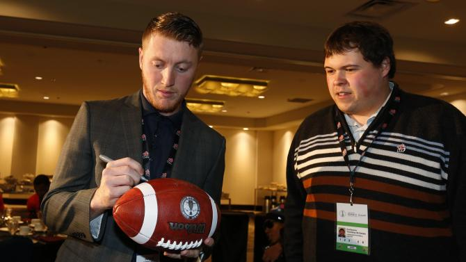 Calgary Stampeders Mitchell signs a football for a fan during their team's lunch at the CFL's 102nd Grey Cup week in Vancouver