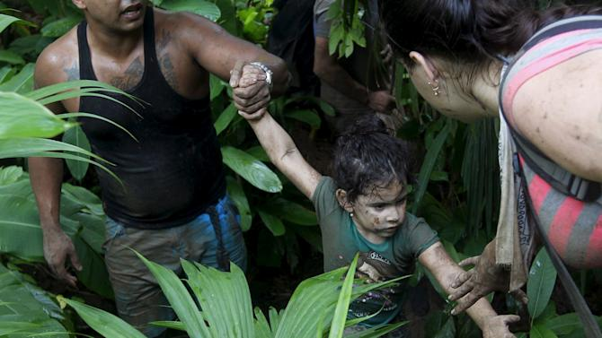 Cuban migrants help a child as they walk down crossing the border from Colombia through the jungle into La Miel, in the province of Guna Yala, Panama