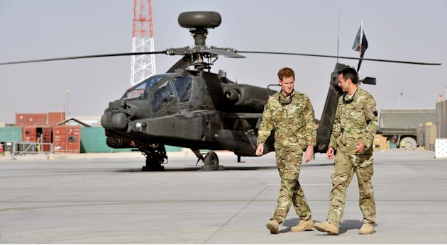 Britain's Prince Harry is shown the Apache flight-line Friday Sept 7 2012 by a member of his squadron (name not provided) at Camp Bastion in Afghanistan, where he will be operating from during his tou