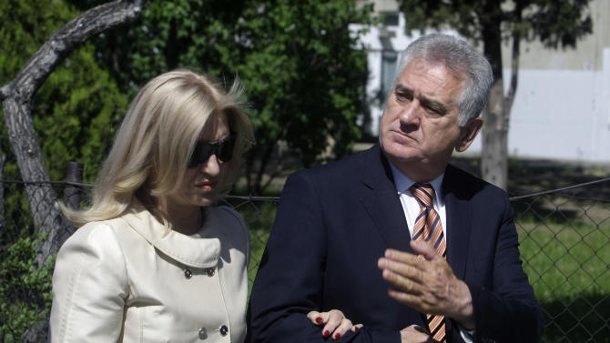 The nationalist Serbian Progressive Party leader and presidential candidate Tomislav Nikolic, right, and his wife Dragica, leave a polling station after casting their votes in Belgrade, Serbia, Sunday, May 6, 2012. Serbia, a landlocked nation of 7.1 million people in southeast Europe, is holding presidential, parliamentary and municipal elections Sunday. Whoever wins could affect Serbia's future relations with the European Union as well as Kosovo, a one-time province whose declaration of independence Serbia has refused to accept. (AP Photo/ Marko Drobnjakovic)