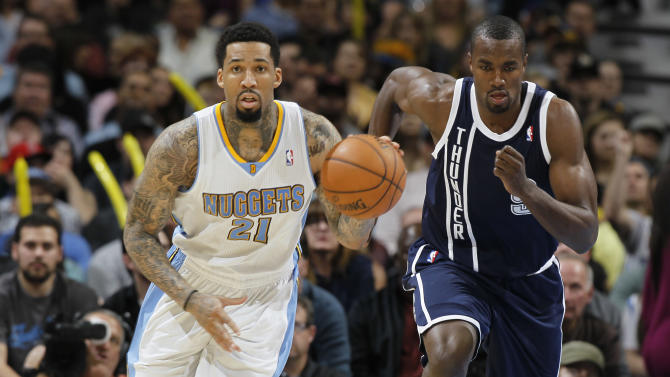 Denver Nuggets forward Wilson Chandler, left, picks up a loose ball in front of Oklahoma City Thunder forward Serge Ibaka, of the Congo, in the third quarter of the Nuggets' 105-103 victory in an NBA basketball game in Denver on Friday, March 1, 2013. (AP Photo/David Zalubowski)