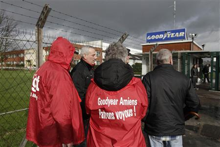 Employees stand at the entrance of the Goodyear tyres factory in Amiens, northern France, in this January 31, 2013 file photo. Maurice Taylor, the CEO of U.S. tyremaker Titan International delivered a crushing resume of how some outsiders view France&#39;s work ethic in a letter saying it would have to be stupid to take over a factory whose staff only put in three hours work a day. Message on jacket reads, &quot;Goodyear Amiens - Gangster Bosses&quot;. Picture taken January 31, 2013. REUTERS/Pascal Rossignol/Files