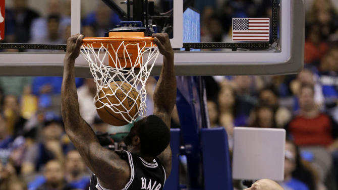 San Antonio Spurs' DeJuan Blair (45) dunks over Dallas Mavericks' Vince Carter (25) and Chris Kaman, right rear, in the first half of an NBA basketball game on Friday, Jan. 25, 2013, in Dallas. (AP Photo/Tony Gutierrez)