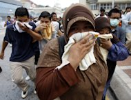 Malaysian activists from Coalition for Clean and Fair Elections (Bersih) cover themselves with towels as they run away from tear gas fired by police during a rally calling for electoral reforms in Kuala Lumpur, Malaysia, Saturday, July 9, 2011. (AP Photo/Lai Seng Sin)