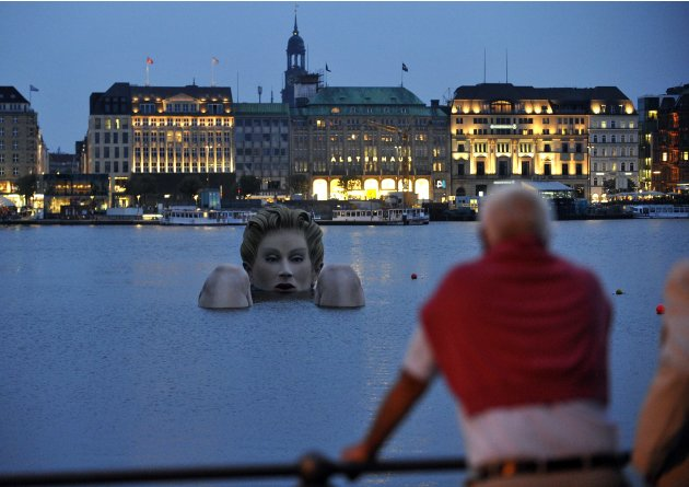 Man looks at a 'mermaid' sculpture created by Oliver Voss in the late evening hours on Alster lake in Hamburg