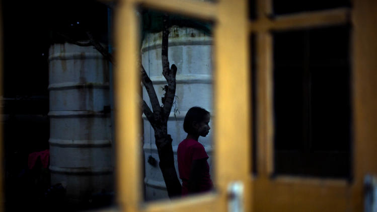 "In this Aug. 29, 2012 photo, reflected in a window, a six-year-old girl Myat Noe Thu, with Burmese local sunscreen ""Thanakha"" applied on her face, stands at a courtyard alone while her HIV-infected parents and younger sister, unseen in the photo, rest in a hut at an HIV/AIDS center on the outskirts of Yangon, Myanmar. Myat is not infected with HIV. Following a half century of military rule, care for HIV/AIDS patients in Myanmar lags behind other countries. Half of the estimated 240,000 people living with the disease are going without treatment and 18,000 are dying from it every year. (AP Photo/Alexander F. Yuan)"