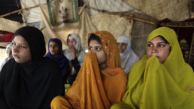 Pakistani women and girls listen to their teacher Mohammad Shiraz, 24, not pictured, during a three hours daily class, teaching illiterate women and children how to read Urdu alphabet and verses of the holy Quran, in a makeshift tent on the outskirts of Islamabad, Pakistan, Tuesday, April 2, 2013. According to the United Nations only 40 percent of Pakistani girls 15 or younger are literate in Pakistan. (AP Photo/Muhammed Muheisen)