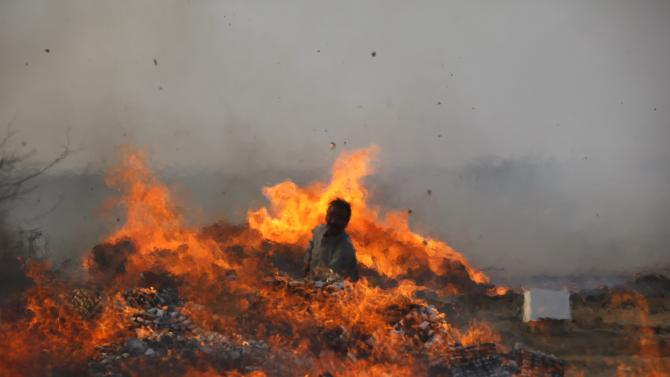 A man from the Pakistan Customs torches a pile of contraband and narcotics on the outskirts of Karachi