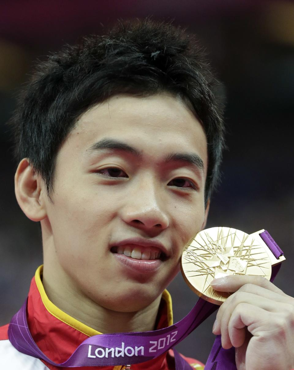 Chinese gymnast Zou Kai displays his gold medal during the podium ceremony for the men's floor exercise finals at the 2012 Summer Olympics, Sunday, Aug. 5, 2012, in London. (AP Photo/Julie Jacobson)