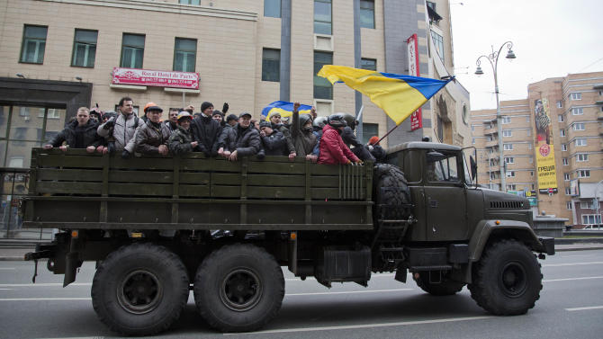 Protesters ride atop of what appears to be a military truck, in central Kiev, Ukraine, Saturday, Feb. 22, 2014. Protesters in the Ukrainian capital claimed full control of the city Saturday following the signing of a Western-brokered peace deal aimed at ending the nation's three-month political crisis. The nation's embattled president, Viktor Yanukovych, reportedly had fled the capital for his support base in Ukraine's Russia-leaning east. (AP Photo/Darko Bandic)
