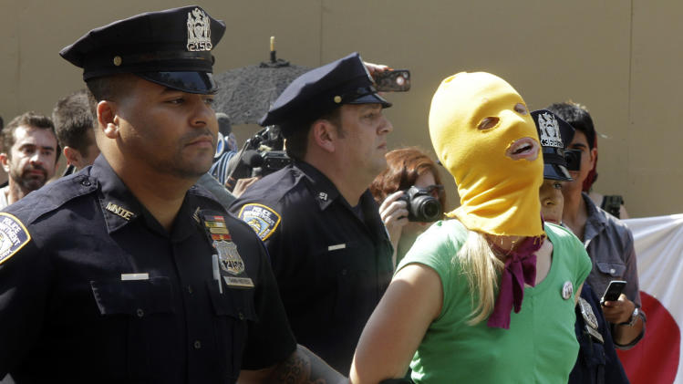 A protester is arrested during a demonstration in front of the Russian consulate in support of Russian punk band Pussy Riot, Friday, Aug. 17, 2012 in New York. A Russian judge found three members of the provocative punk band guilty of hooliganism on Friday, in one of the most closely watched cases in recent Russian history. The three were arrested in March after a guerrilla performance in Moscow's main cathedral calling for the Virgin Mary to protect Russia against Vladimir Putin, who was elected to a new term as Russia's president a few days later. (AP Photo/Alex Katz)