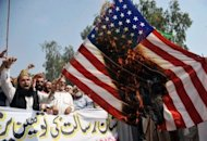 Pakistani Muslim protesters burn a US flag during a rally against an anti-Islam movie in Peshawar. Al-Qaeda said a deadly attack on US diplomats in Libya was in revenge for the killing of its number two, monitors reported