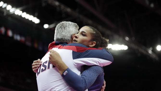 U.S. gymnast Alexandra Raisman hugs coach Mihai Brestyan after her performance on the beam during the artistic gymnastics women's apparatus finals at the 2012 Summer Olympics, Tuesday, Aug. 7, 2012, in London. (AP Photo/Gregory Bull)